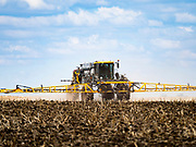 "20 APRIL 2020 - BOUTON, IOWA: A spreader applies fertilizer to a field near Bouton. Iowa farmers are prepping their fields for the 2020 season. The relatively mild winter and dry spring has allowed farmers to get into their fields 1 - 2 weeks earlier than last year. Farmers and agricultural workers are considered ""essential"" workers in Iowa and not subjected to the coronavirus restrictions nonessential workers are. Farmers usually work by themselves, and social distancing guidelines have not impacted them as much as it has workers in Iowa's cities.   PHOTO BY JACK KURTZ"