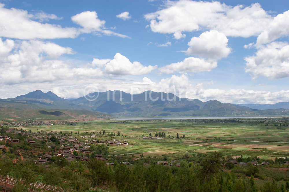 Wide open landscape of a flat plain looking towards distant mountains near to Lijiang, Yunnan, China.