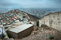 NO WEB/NO APPS - (Text available) General view of the 'Wall of shame' (Muro de la Verguenza) which divides the Districts of Santiago de Surco and San Juan de Miraflores in the city of Lima, Peru in May 2017. In Peru's capital Lima, a three-meter-high concrete wall topped with reels of razor wire separates two areas. The so-called 'Wall of Shame' - sometimes nicknamed 'Peru's Berlin Wall' - divides the urbanisation of Las Casuarinas, where some of the country's richest inhabitants live, and the poor suburb of Vista Hermosa next door. It was initially put up over fears that the inhabitants from the poor neighbourhood would steal from wealthy fellow citizens living nearby. On the rich side of the wall, the price for a square meter can exceed 2,000 dollars. To enter the area, you must show your ID to the guards watching the gate at the bottom of the hill. Former high-ranking politicians and bank directors live here. Their houses are surrounded by lush gardens and swimming pools despite the scarcity of water. Meanwhile, on the San Juan de Miraflores side, residents often fall victim to robbery and theft. They live in houses of barely 25m², made from scrap material, surrounded by the sand and earth characteristic of Lima's desert landscape. Photo by Giacomo D'Orlando/ABACAPRESS.COM