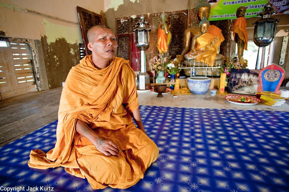 Apr. 3, 2010 - KHUN SAMUTCHINE, THAILAND: Abbot ATHIKARN SOMNUK ATIPANYO, in the prayer hall at Wat Samutchine. Rising sea levels brought about by global climate change threaten the future of Khun Samutchine, a tiny fishing village about 90 minutes from Bangkok on the Gulf of Siam. The coastline advances inland here by about 20 metres (65 feet) per year causing families to move and threatening the viability of the village. The only structure in the village that hasn't moved, their Buddhist temple, is completely surrounded by water and more than 2 kilometers from the village. The temple and the village have asked the Thai government and several NGOs for help, but the only help so far is a narrow concrete causeway the government is building that will allow people to walk into the temple from a boat landing two miles away. The walk to the village from a closer boat landing is shorter, but over an unimproved mud flat that is nearly impassible in the rainy season.  PHOTO BY JACK KURTZ