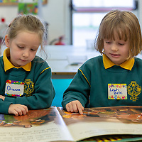 Orianna Nic Sheain and Leah Belle Ní Dhubháin read some books at their first day of school at Gaelscoil Mhíchíl Cíosóg, Inis