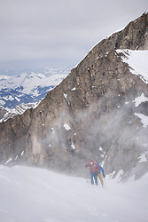 Ski mountaineers climbing on snowy mountain in snow storm, Zell Am See, Austria