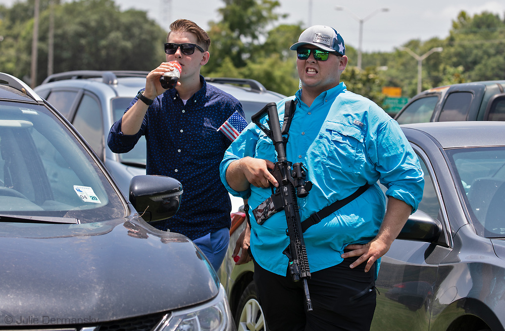 """Security guard with a long gun at a """"Save America Rally"""" in Baton Rouge on the 4th of July across the street from the Governor's Mansion where about 200 gathered. The 4th of July rally was organized by Jeff Crouer, Mimi Owens and Woody Jenkins, chairman of the executive committee for the Republican Party in East Baton Rouge Parish. Rev. Tony Spell of Life Tabernacle Church who has held church services in defiance of a stay-at-home order throughout the pandemic was one of the speakers. He an other speakers expressed their displeasure of being told to wear a mask to prevent the spread of Covid-19 and the removal of confederate monuments."""