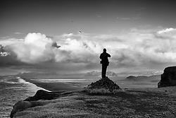 Photographer standing on top of a hill, watching towards the mountains in Myrdalur - Ljósmyndari horfir til fjalla