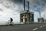 Fietsers rijden over de Oosterscheldekering tussen Schouwen-Duiveland en Noord-Beveland. De Oosterscheldekering is vormt waterkering en is onderdeel van de Deltawerken waarmee Nederland beschermt wordt tegen overstromingen bij springvloed.  <br /> <br /> Cyclists pass the Oosterscheldekering between Schouwen-Duiveland and Noord-Beveland. The Oosterscheldekering is a flood defense system and is part of the Delta Works that protects the Netherlands against flooding in the event of a flood.