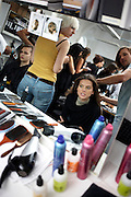 Make-up and hair stylists ready models at British couture designer Margaret Howell's Autumn fashion show in her design studio