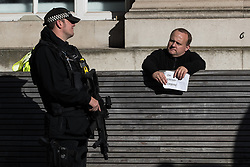 """© Licensed to London News Pictures  . 03/10/2017 . Manchester , UK . Man holding """" OH JEREMY CORBYN """" sign , talking to armed police outside Manchester Central Library , amongst protesters outside the conference , on day three of the Conservative Party Conference at the Manchester Central Convention Centre . Photo credit : Joel Goodman/LNP"""