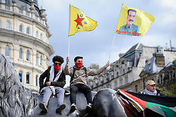 © Licensed to London News Pictures. 01/05/2018. LONDON, UK.  Demonstrators atop a Trafalgar Square lion wave flags during the annual May Day Rally on International Workers' Day. People marched through central London to a rally in Trafalgar Square.  Photo credit: Stephen Chung/LNP