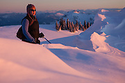 Julia Wentzel contemplates the sunset views from a snowy, windswept ridge above Paradise in Mount Rainier National Park.