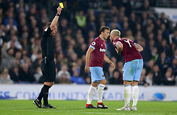 West Ham United's Marko Arnautovic (right) receives a yellow card from Referee Kevin Friend after fouling Brighton & Hove Albion's Beram Kayal (not in frame)