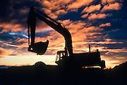 Alaska. Silhouette of a excavator at sunset.