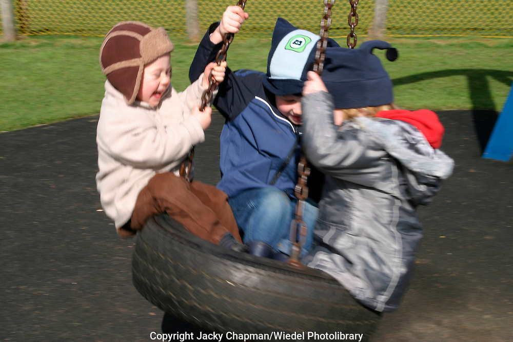 Three young children swinging  playing and laughing on a swing made of car tire.