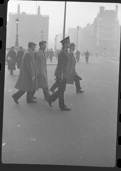 Peter Hughes in Guard Uniform.   B269..1960..06.01.1960..01.06.1960..6th January 1960..Pictured strolling through Dublin was Mr Peter Hughes resplendent in his Guards Uniform...Image taken as Peter crosses O'Connell Street on O'Connell Bridge / Eden Quay junction.