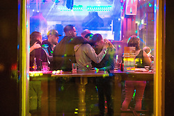 © Licensed to London News Pictures . 11/09/2016 . Manchester , UK . View through the window of men hugging close together , inside Yates Wine Lodge on Portland Street . Revellers out in Manchester City Centre . Photo credit : Joel Goodman/LNP