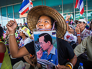 """08 APRIL 2014 - BANGKOK, THAILAND:  A Thai anti-government protestor holds up a picture of Bhumibol Adulyadej, the King of Thailand, while she blocks the entrance to the Ministry of Justice. Several hundred anti-government protestors led by Suthep Thaugsuban went to the Ministry of Justice in Bangkok Tuesday. Suthep and the protestors met with representatives of the Ministry of Justice and expressed their belief that Thai politics need to be reformed and that corruption needed to be """"seriously tackled."""" The protestors returned to their main protest site in Lumpini Park in central Bangkok after the meeting.   PHOTO BY JACK KURTZ"""