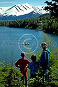 Alaska. Kenai Peninsula. Jacky Graham and twins Alex and Marina watch as rafters pass by on the Kenai Lake near Cooper Landing. MR.