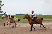 Two Gaucho men racing on horses at a Gaucho Estancia In Lujan, Argentina. .