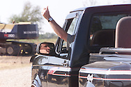 Texas Governor and Republican presidential candidate George W. Bush is reflected in the rear view mirror as he gives a thumbs up to a visitor as he leaves in his pickup from his new house, still under construction, while relaxing on his rural Crawford, Texas ranch September 16, 2000.  Rick Wilking