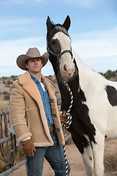 handsome cowboy with a painted horse on a ranch
