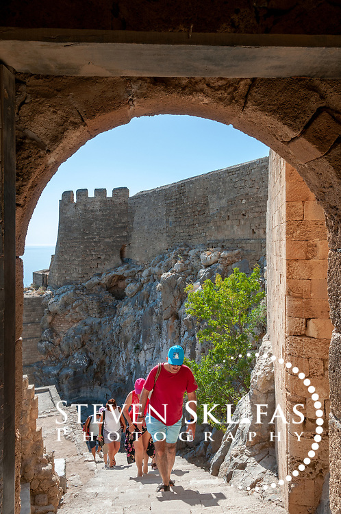 Rhodes. Greece. View of people walking up the steep stairway towards the arched entrance of the Castle of the Knights of St John on the 114 metre high Acropolis hill at Lindos. The stairway and castle were built by the Knights between 1421 and 1503.