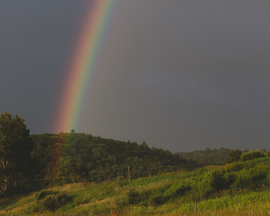 A vibrant rainbow rising out from the Vermont landscape on a summer afternoon.