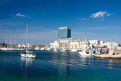 Una barca a vela rientra a pomeriggio inoltrato nel porto di Gallipoli (LE)