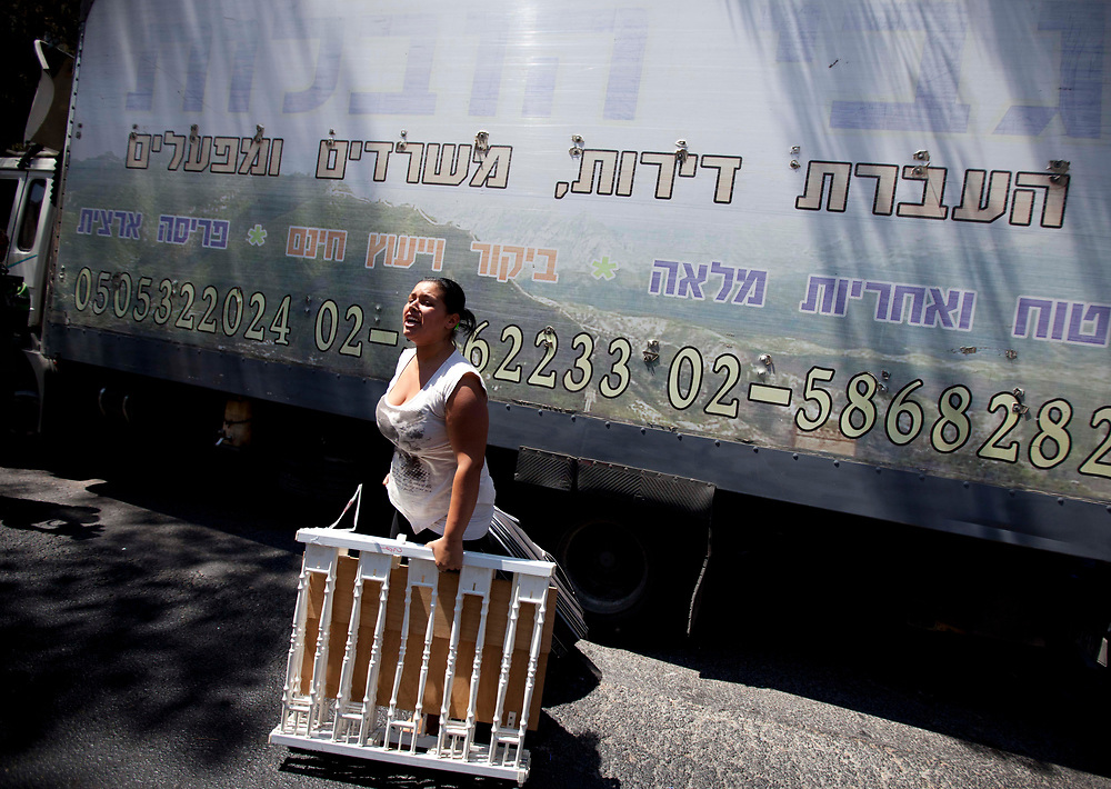 An Israeli homeless woman cries and expresses her anger at Israeli police (not pictured) as she holds an item of her personal belongings near an abandoned student dormitory building owned by the Hebrew University, in the Jerusalem neighborhood of Kiryat HaYovel, on September 13, 2011, after security forces evicted homeless families who broke into the building a week and a half ago and took over it, demanding public housing solutions.