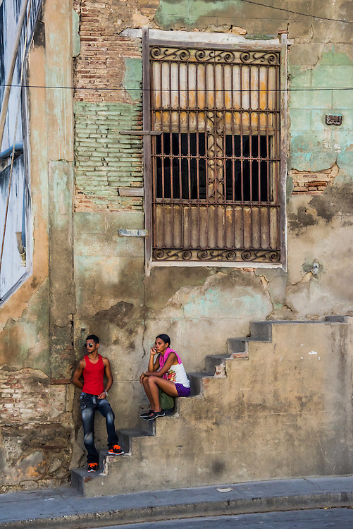 A couple waits on a set of steps in front of a building in Santiago, Cuba