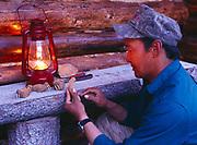 Yupik carver, Elia Abruska, carving walrus from cottonwood bark, cabin at the Anvik River Lodge northwest of Anvik, Alaska.