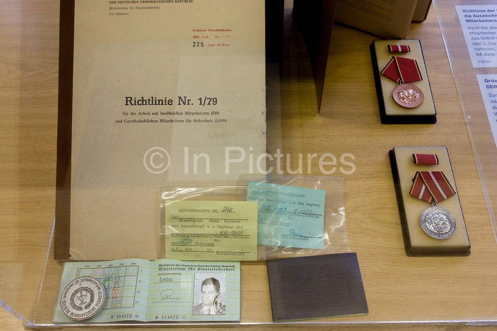 ID papers for an anonymous secret agent from Cottbus, Germany, an exhibit in the ministerial headquarters of the Stasi secret police in Communist East Germany, the GDR. Built in 1960, the complex now known as the Stasi Museum. Between 1950 and 1989, the Stasi employed a total of 274,000 people in an effort to root out the class enemy. Before the fall of the Wall, it was a 22-hectare complex of espionage whose centrepiece is the office and working quarters of the former Minister of State Security, Erich Mielke who considered their role as the 'shield and sword of the party', conducting one of the world's most efficient spying operations against its political dissenters during its 40-year old socialist history. The Stasi Museum is a 22-hectare complex of research  and memorial centre concerning the political system of the former East Germany.
