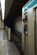Subway train conductor looking down the platform from the train window. Kyoto, Japan