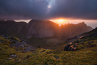 Evening sun breaks though clouds over mountains from the summit of Markan (602m), Moskenesøy, Lofoten Islands, Norway