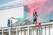 Birmingham, United Kingdom, June 15, 2021: Palestine Action activists hold a flare as they walk on the rooftop of the bulding they occupied, while Members of Protestor Removal Police Unit are seen entering the Arconic site factory in Birmingham on Tuesday, June 15, 2021. (VX Photo/ Vudi Xhymshiti)