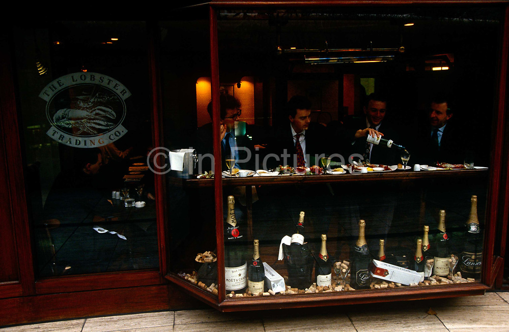Four associates celebrate a successful day's business by treating themselves to a lunchtime bottle of white wine amid the scenes of prosperity and wealth of early 90s Britain. At their feet in the bay window are the fruits of a buoyant economy - Magnums of and jeroboams of Champagne to help revel in the success of the era. This is the City of London, the heart of the capital's financial district where money is earned in great quantities and commodities traded in their millions. The commissions are huge and lunchtimes are extravagant.
