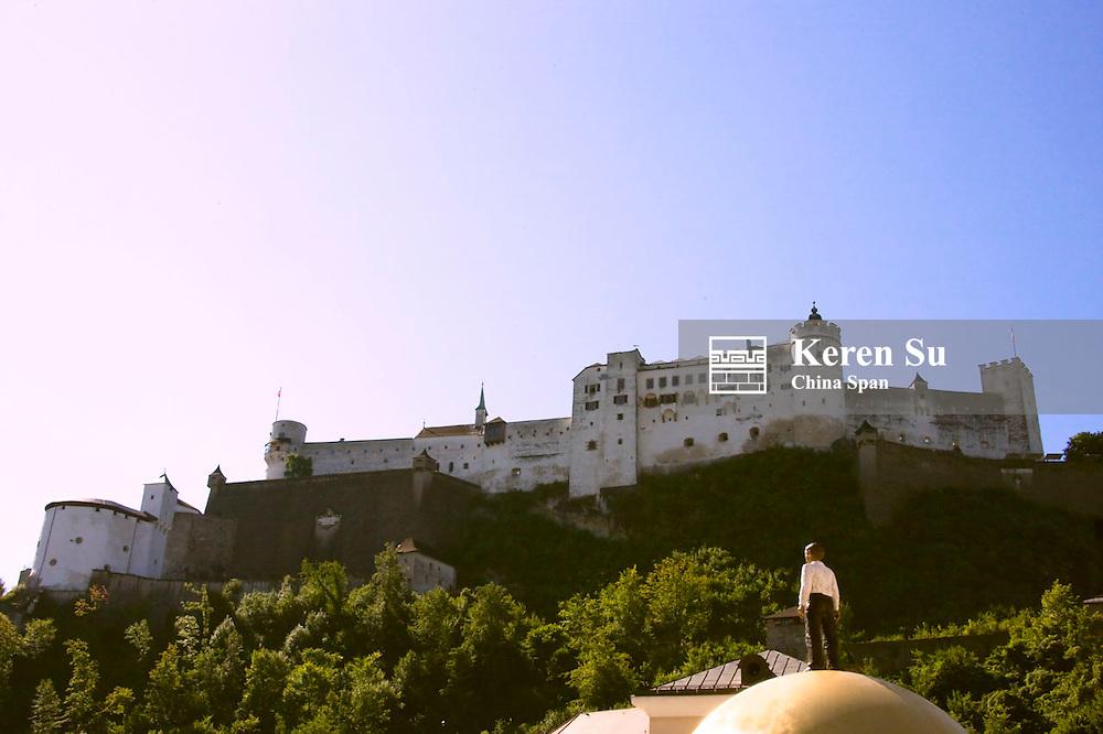 Man on the golden globe, Fortress Hohensalzberg above, Salzburg, Austria