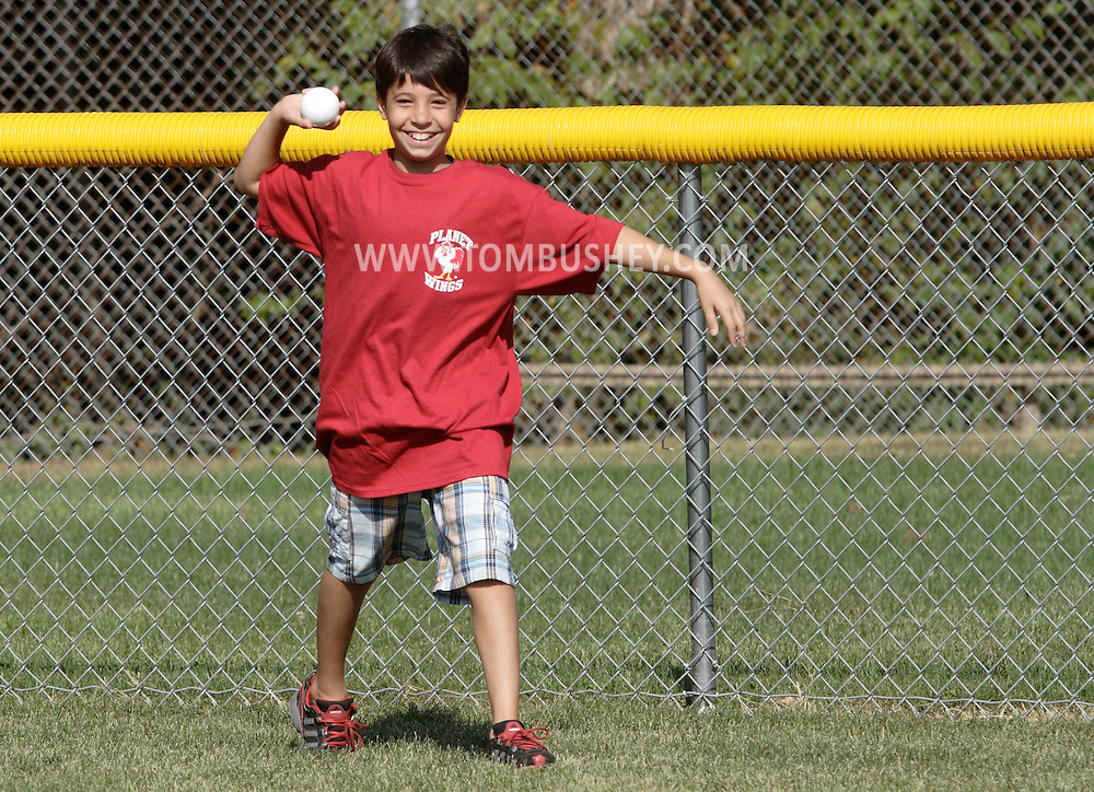 Scotchtown, New York - A boy smiles after making a catch in the outfield during the Wiffle for Kids charity Wiffle Ball tournament at the Town of Wallkill Little League fields on Sept. 25, 2010.