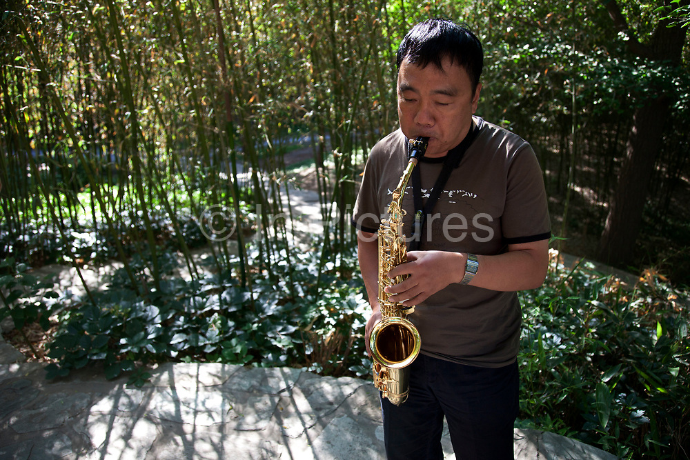 Man playing the saxophone in Zizhuyuan Park in Beijing, China. This park is well known as a place where middle aged or elderly Chinese come. This can take all forms including some surprising ones. Purple Bamboo Park (Zi Zhu Yuan Gongyuan) also called Zizhuyuan Park or Black Bamboo Park largest parks in Beijing. It is located in the Haidian District. The park consist of three connecting lakes covering over a total area of 48 hectares. Typical of the classical Chinese garden style, and like many of Beijing's parks and gardens, it is a mountain-water landscaped garden. Constructed around canals and large lakes, the Bamboo Park is known for its liberal use of verdant bamboo groves. The garden has a variety of bamboos on display. Young people also believe that if they go to the park as a couple that their relationship is doomed to fail.