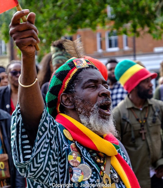 Rastafarian men dancing to and enjoying Groundation music at annual Reparations Revolution event on Afrikan Emancipation Day in Windrush Square Brixton 2021.