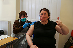 © Licensed to London News Pictures. 22/10/2021. London, UK. A 42 year old woman gestures as Nassima Larbi, a NHS vaccinator, administers the Pfizer/BioNTech (Comirnaty) Covid-19 vaccine at a vaccination centre in north London. According to the experts, the Covid-19 booster jab uptake is too low amid fears of further restrictions this winter as coronavirus cases rise. The Government is considering cutting the interval between booster jabs and the second dose of a Covid-19 vaccine from six month to five months. Photo credit: Dinendra Haria/LNP