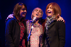 © Licensed to London News Pictures . 15/09/2013 . Bury , UK . SINEAD O'CONNOR (centre) shares the microphone with her backing singers as the closing act of the Ramsbottom Festival , in Bury , this evening (Sunday 15th September) . The singer made headlines recently after revealing new tattoos of the letters B and Q on each of the cheeks of her face . Photo credit : Joel Goodman/LNP