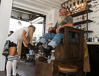 Dave Nelson of Portland, ME gets a boot shine from Aerinn Schlenkov at the Progressive booth housing Flo's Chop Shop Thursday afternoon on Lakeside Avenue.  (Karen Bobotas/for the Laconia Daily Sun)