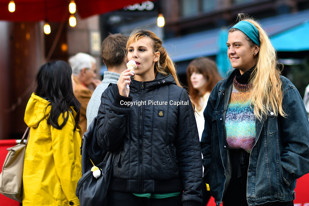 A lady eating ice-cream and dancing watching a Japanese lady dance at Leicester Square, London, UK 23 September 2018.