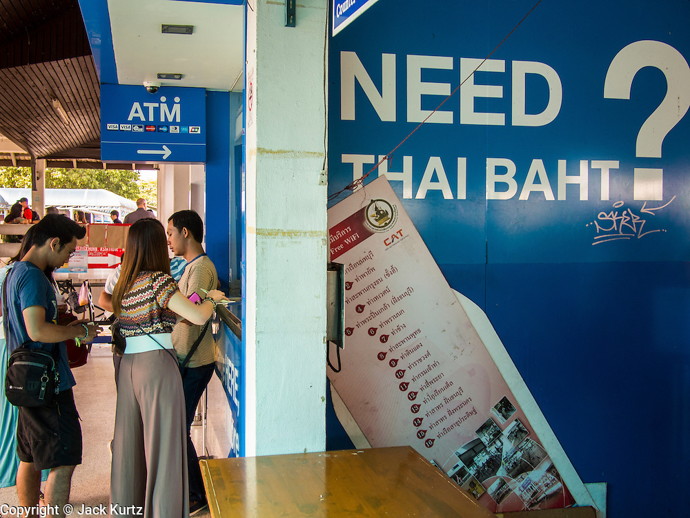 """23 AUGUST 2013 - BANGKOK, THAILAND:    Tourists line up at a TMB Exchange Booth at Saphin Taksin/Central Pier to exchange their currencies for Thai Baht. Thailand entered a """"technical"""" recession this month after the economy shrank by 0.3% in the second quarter of the year. The 0.3% contraction in gross domestic product between April and June followed a previous fall of 1.7% during the first quarter of 2013. The contraction is being blamed on a drop in demand for exports, a drop in domestic demand and a loss of consumer confidence. At the same time, the value of the Thai Baht against the US Dollar has dropped significantly, from a high of about 28Baht to $1 in April to 32THB to 1USD in August.    PHOTO BY JACK KURTZ"""