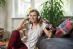 Young woman listening to music and drinking wine in living room, Munich, Bavaria,