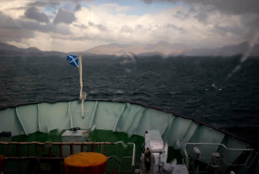 LEWIS AND HARRIS, SCOTLAND - CIRCA APRIL 2016: Ferry boat approaching the islands of Lewis and Harris and the Port of Tarbert under rain in the outer islands of Lewis and Harris in Scotland.