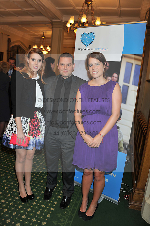 Left to right, PRINCESS BEATRICE OF YORK, MARK WADDINGTON Chief Executive Hope and Homes for Children and PRINCESS EUGENIE OF YORK at a reception for The Mirela Fund in partnership with Hope and Homes for Children hosted by Natalie Pinkham in The Churchill Room, House of Commons, London on 30th April 2013.