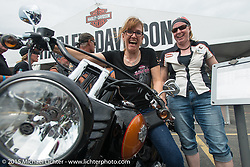 Tessa Fidler of Oxford England checks out a 2015 Slim with the help of Harley-Davidson's Brenda Schuetten at the HD display during the 75th Annual Sturgis Black Hills Motorcycle Rally.  SD, USA.  August 4, 2015.  Photography ©2015 Michael Lichter.