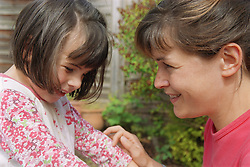 Young girl with autism being tickled by mother,