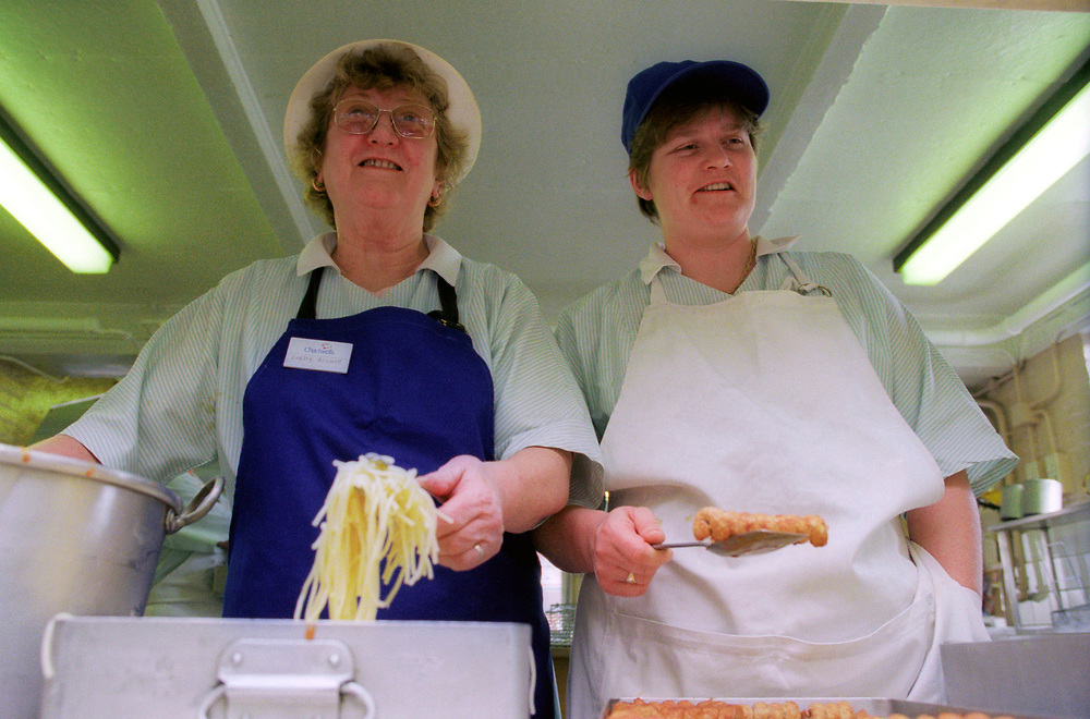 Dinner ladies in a London primary school dishing out food to pupils,