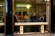 Businessmen sip morning coffee in one of the many cafes in the financial district of the capital called the Square Mile, also the oldest area of London named by the Romans. Five gentlemen wearing suits drink or talk in the window of this bar near the Bank of England. Coffee meeting places were the first calling-in place during the 18th century when the news and gossip of the day were discussed at great length and where deals were done and businesses started, included newspapers and the traditional British pub.